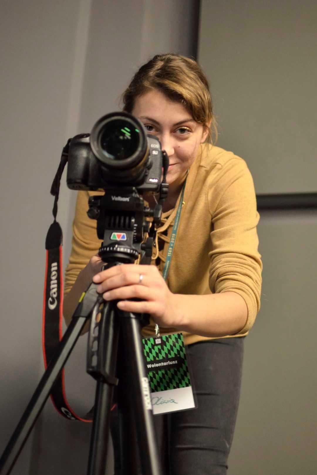 uśmiechnięta dziewczyna z aparatem na statywie